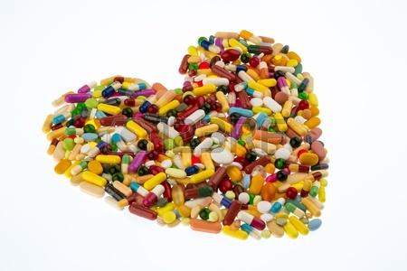 19088914-kleurrijke-tabletten-gerangschikt-in-hartvorm-symbool-voor-hart-en-vaatziekten-medicatie-en-geneesmi